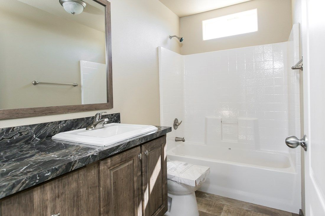 The 2022 COLUMBIA RIVER Guest Bathroom. This Manufactured Mobile Home features 3 bedrooms and 2 baths.